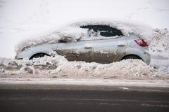 De auto, met dikke laag van sneeuw en modder, op de rijweg wordt behandeld die royalty-vrije stock foto