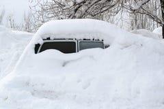 De auto, met dikke laag van sneeuw wordt behandeld die Negatief gevolg van zware sneeuwval stock foto