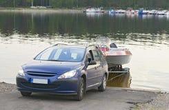 De auto met een boot op de aanhangwagen Stock Foto