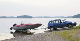 De auto met een boot op de aanhangwagen Royalty-vrije Stock Afbeeldingen