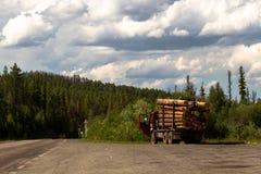 De auto met hout wordt geladen is op de weg die Royalty-vrije Stock Fotografie