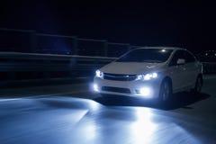 De auto met xenonkoplampen drijft snel nigh op weg bij Stock Afbeelding