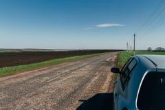 De auto is op de weg De zomerweg waarop er een geparkeerde auto is Het reizen door auto Stock Foto