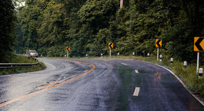 De auto's die op weg lopen het regenden, is de weg glad Stock Afbeeldingen