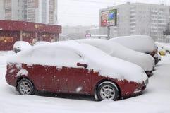 De auto's door sneeuw, tribune op een wegkant van de weg die worden gebracht. Royalty-vrije Stock Afbeeldingen