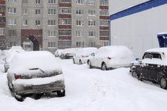 De auto's door sneeuw, tribune op een wegkant van de weg die worden gebracht. Stock Foto