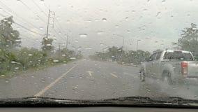 De auto's lopen op de straat op een regenachtige dag en gebruiken een wisser bij de voorzijde stock videobeelden