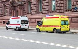 De auto's van de noodsituatieziekenwagen met blauw opvlammend licht op de dakpa Stock Afbeeldingen