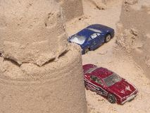 De auto's van het stuk speelgoed in zandkasteel Stock Afbeeldingen