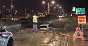 De auto valt onderaan reusachtig gat in straat stock video