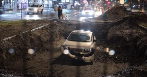 De auto valt onderaan reusachtig gat in straat stock videobeelden