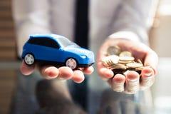 De Auto van Businesspersonholding small blue en Gouden Muntstukken royalty-vrije stock foto
