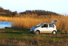 De auto van de familie bij de rivieroever, in zonsonderganglicht Royalty-vrije Stock Foto