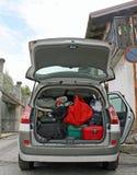 De auto van de familie klaar om met het boomstamhoogtepunt van koffers te gaan Stock Foto's