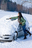 De auto van de winter - de vrouw verwijdert sneeuw uit windscherm Royalty-vrije Stock Foto