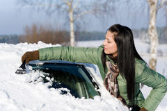 De auto van de winter - de vrouw verwijdert sneeuw uit windscherm Royalty-vrije Stock Afbeelding