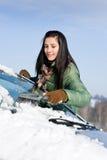 De auto van de winter - de vrouw verwijdert sneeuw uit windscherm Stock Afbeelding