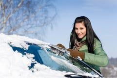 De auto van de winter - de vrouw verwijdert sneeuw uit windscherm Stock Foto