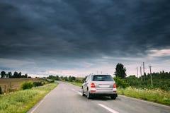 De Auto van Gray Luxury SUV bij de Landweg bij Zomer Bewolkte Hemel boven Asphalt Motorway, Weg Stock Foto's