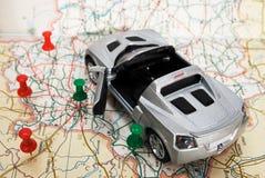 De auto van het stuk speelgoed op een geografische atlas Stock Fotografie