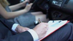 De auto van het vrouwenparkeren, het mannelijke examen van het het rapport rijbewijs van de instructeurs vullende controlelijst stock video