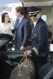 De Auto van pilootkeeping luggage in Stock Afbeeldingen