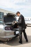 De Auto van zakenmanunloading luggage from bij Luchthaven Stock Foto's