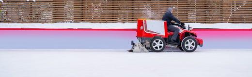 De auto voor het oppoetsen van de ijsoppervlakte van de ijsbaan voor de ritten van het de wintervermaak en herstelt het ijs stock foto