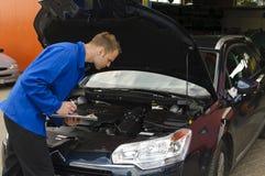 De auto werktuigkundige controleert een voertuig Stock Foto