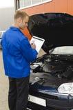 De auto werktuigkundige controleert een voertuig Stock Foto's