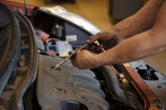 In de auto, worden de kaarsen vervangen, maakt de bestuurder van deze auto reparaties stock fotografie