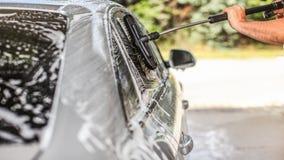 De auto in zelf wordt gewassen dient carwash op een zonnige dag die Detail van glas van het borstel het schoonmakende die zijruit royalty-vrije stock foto