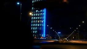 De autoaandrijving tegen de achtergrond van de bouw Avondnacht De langzame motie vangt blauw licht stock footage