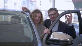 De autoaankoop, glimlachend paar in liefde nieuwe automobiele eigenaars geniet van kopend en toont sleutels in autowinkel stock footage