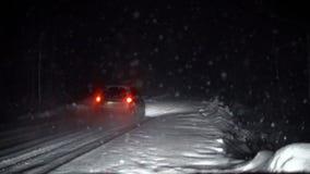 De autobewegingen langs de sneeuwweg bij nacht stock footage