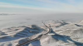 De autobewegingen op de weg onder de sneeuwheuvels Uren en landschap Weg Alma Ata-Bishkek kazachstan stock video