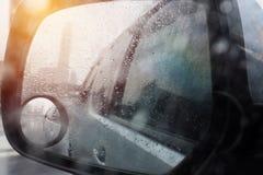 De autobezinningen van regendruppeltjes door achteruitkijkspiegel Stock Foto's