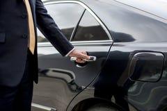 De Autoconcept van zakenmanhandle limousine door royalty-vrije stock afbeelding