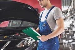 De autodienst, reparatie, onderhoud en mensenconcept - auto mechanische mens of Smith met klembord op workshop royalty-vrije stock foto's