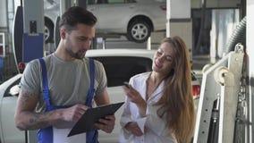 De autodienst, reparatie, overeenkomst en mensenconcept - werktuigkundige en klant of autoeigenaar die document het schudden hand stock video