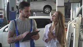 De autodienst, reparatie, overeenkomst en mensenconcept - werktuigkundige en klant of autoeigenaar die document ondertekenen op w stock footage