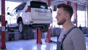 De autoeigenaar geeft sleutels en schudt handen aan de mannelijke werktuigkundige, portret van een gelukkige arbeider op achtergr stock footage