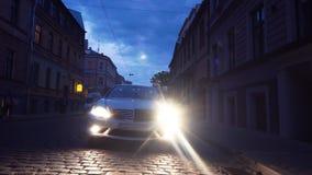 De autoeinden op cobbles de stadsstraat van de bestratings twighlight nacht, mensen stapt op stock footage
