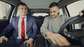 De autohandelaar geeft FOB sleutel aan vrolijke mannelijke koper, binnen schudden de mensen handen, het glimlachen en het spreken stock video
