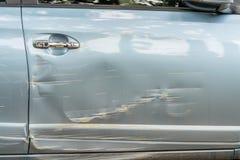 De autokant is gekrast en geschaafd met diepe schade aan de verf stock fotografie