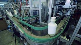 De automatische vervoerder vestigt witte plastic flessen opnieuw stock footage