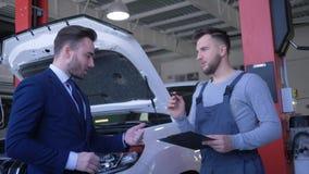 De autoreparatiewerkplaats, mannelijke cliënt overhandigt voertuigsleutels aan hersteller voor professioneel onderhoud en schudt  stock footage