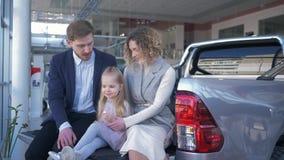 De autosalon, jonge familie met kind kiest voertuig en communiceert met elkaar terwijl het zitten in boomstam bij auto stock videobeelden