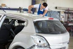 De autoschilder poetst krassen op auto op royalty-vrije stock foto's