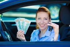 De autosleutels van de vrouwenholding, dollarrekeningen, zitting in haar nieuwe auto Royalty-vrije Stock Foto
